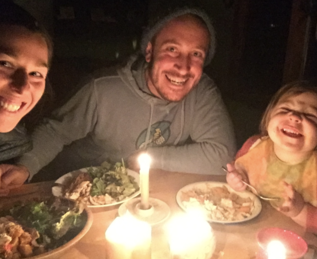 A family in candlelight smiling