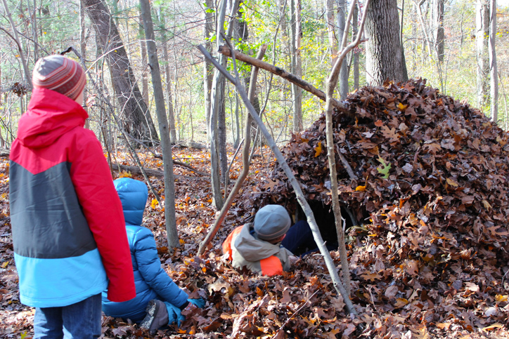 Campers making a fort from leaves and sticks