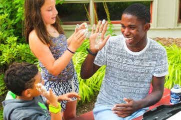 Counselor giving a messy high five to campers