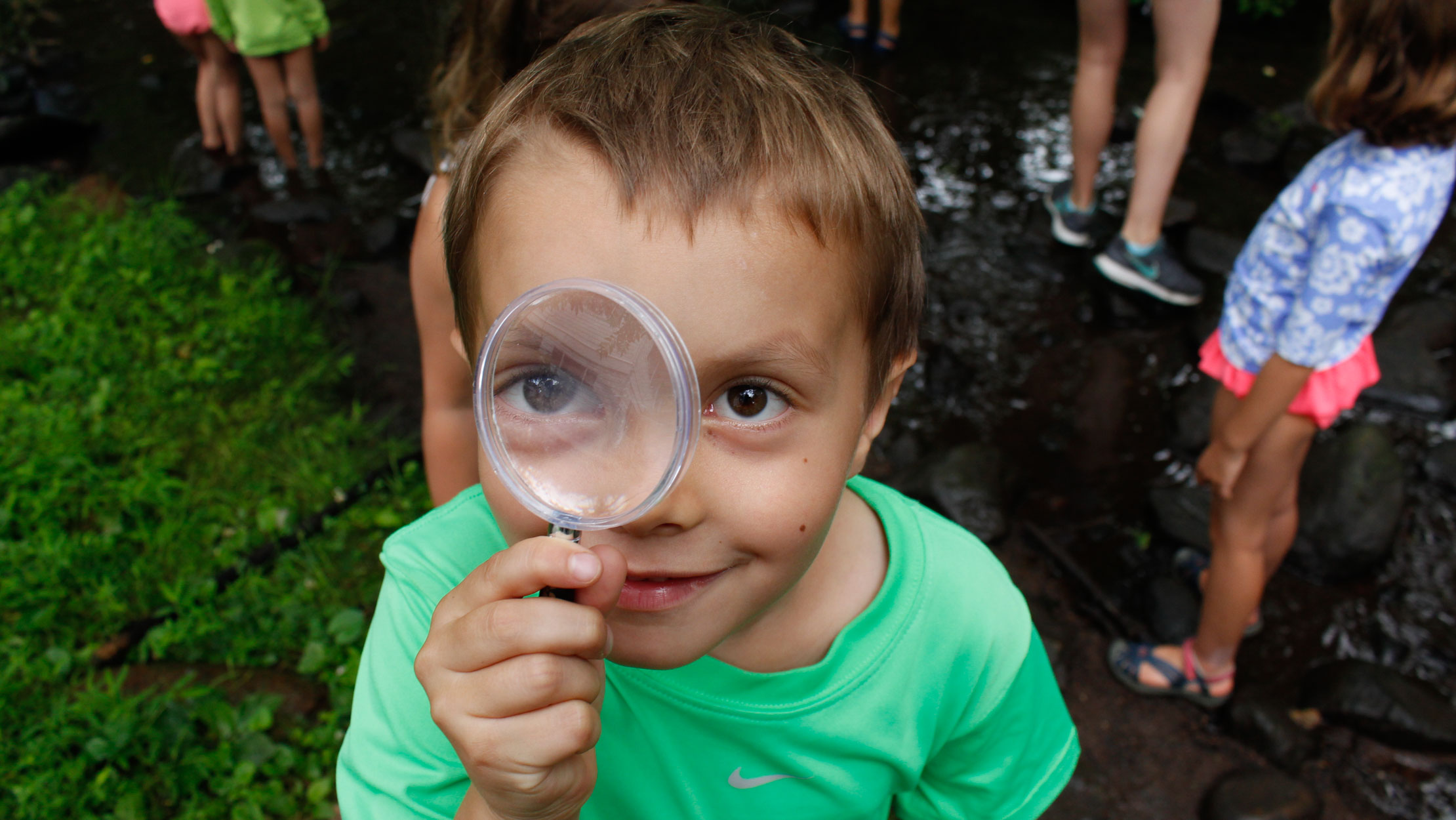 Young camper looking through a magnifying glass