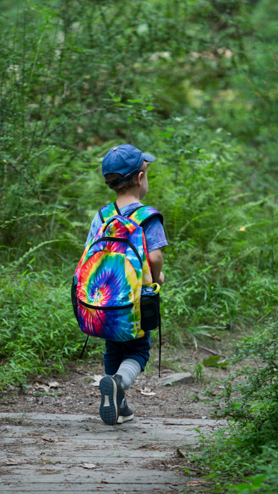 Young camper with backpack walking in the woods