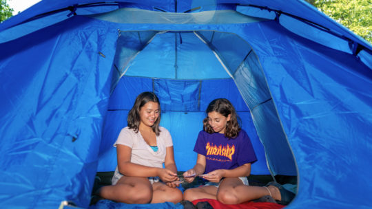 Campers playing cards in a tent