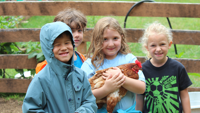 Group of campers holding a chicken