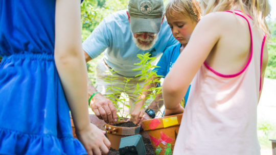 Campers doing crafts with plant pots
