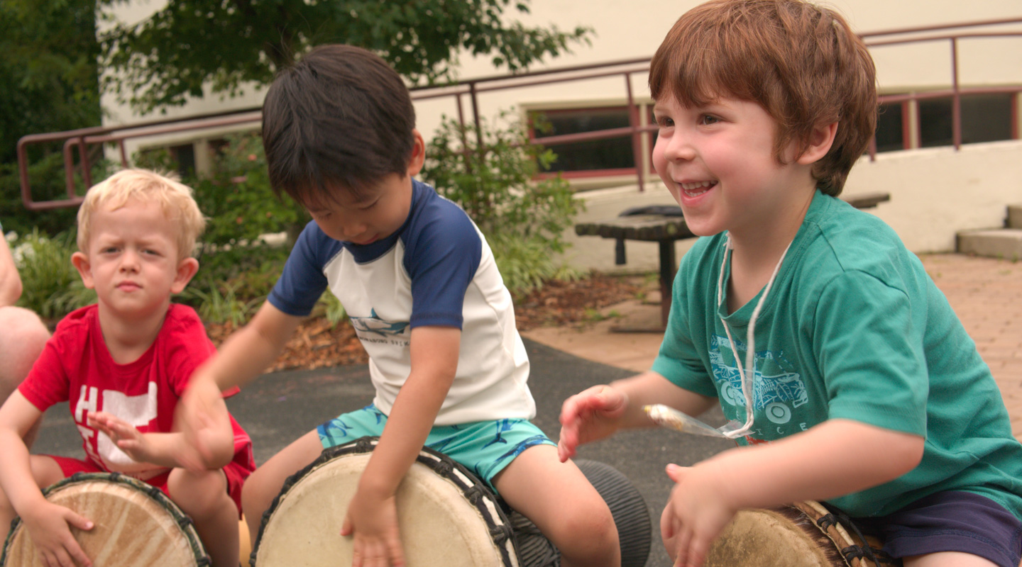 Young campers drumming on drums
