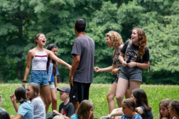 Campers singing and dancing in the grass