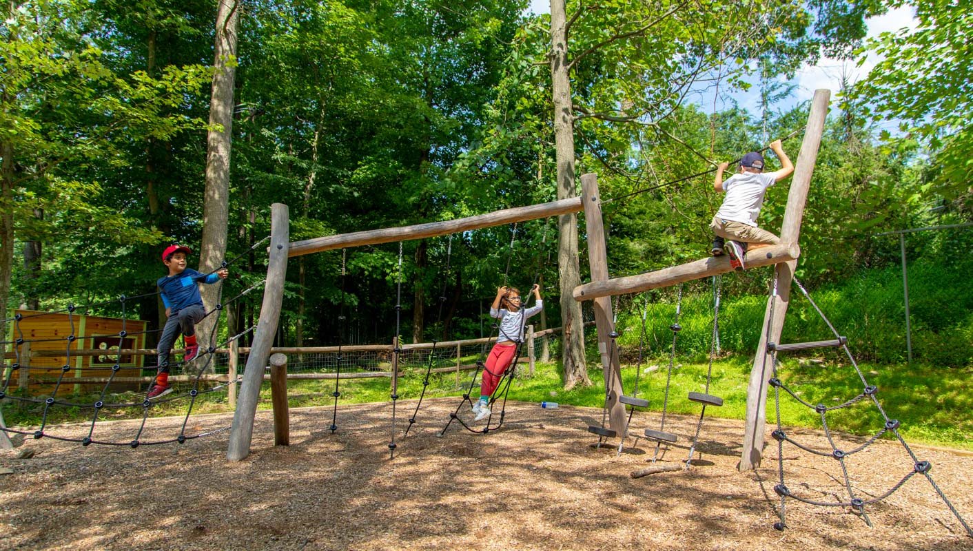 Campers playing on the outside jungle gym