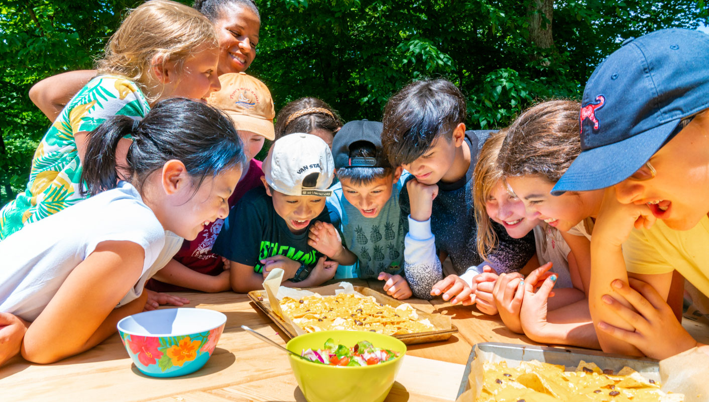 Campers gathered around a plate of nachos