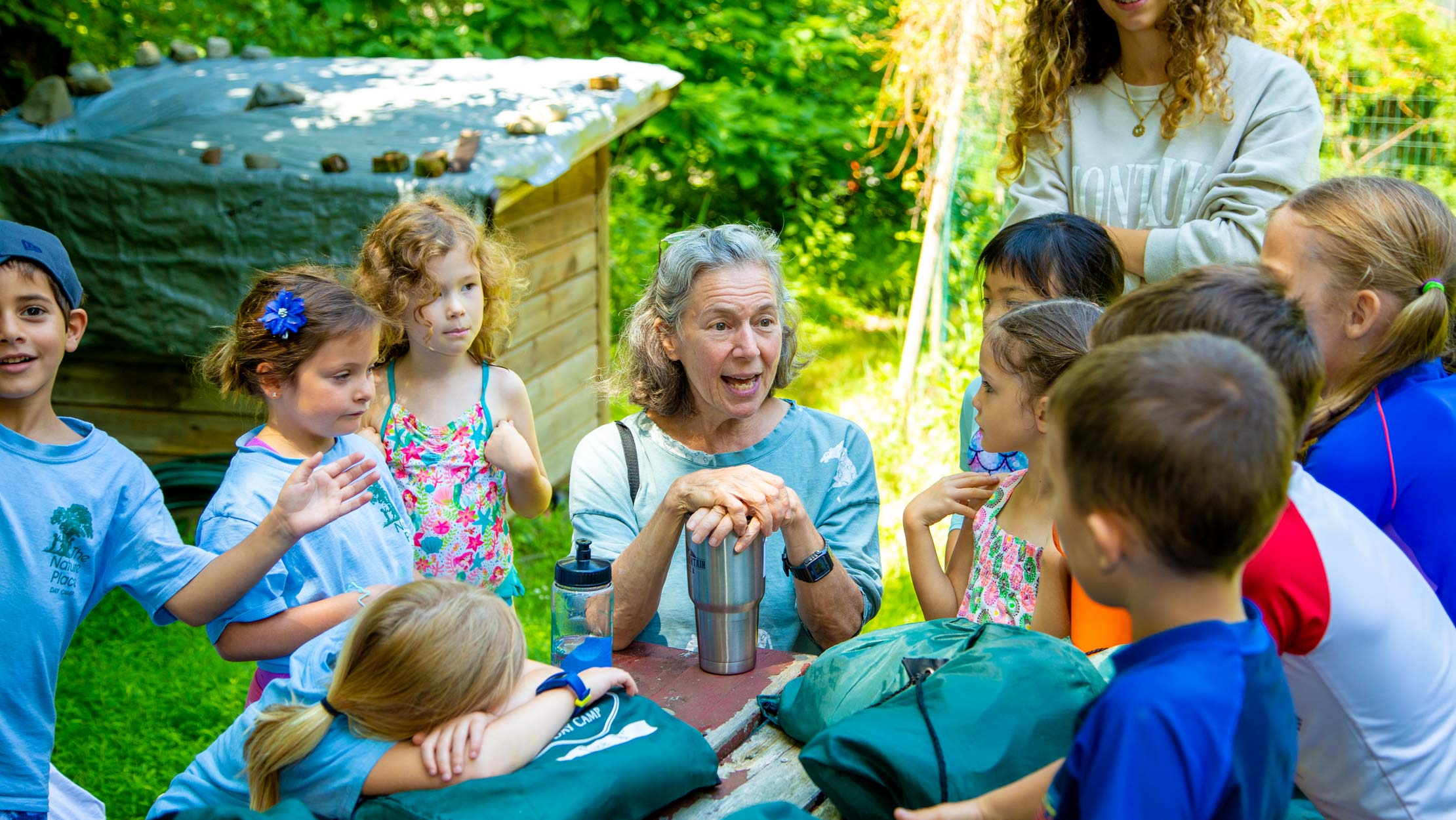 Campers gathered around a counselor listening