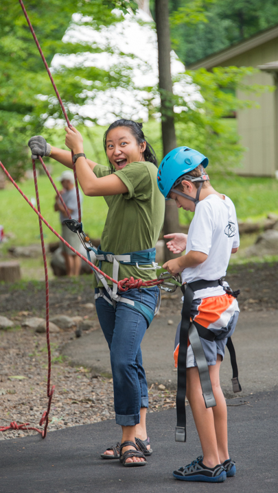 Counselor working the ropes for the rock wall
