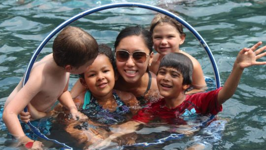 Campers and counselor swimming in the pond